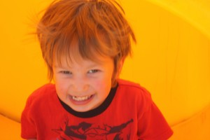 A 3-year-old boy wearing a red shirt with a huge grin on his face